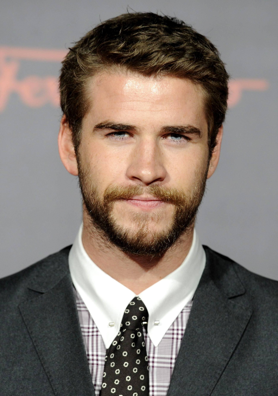 Coupe de cheveux Ivy League: Liam Hemsworth aux cheveux bruns dans une coupe de cheveux texturée Ivy League, vêtu d'un costume gris