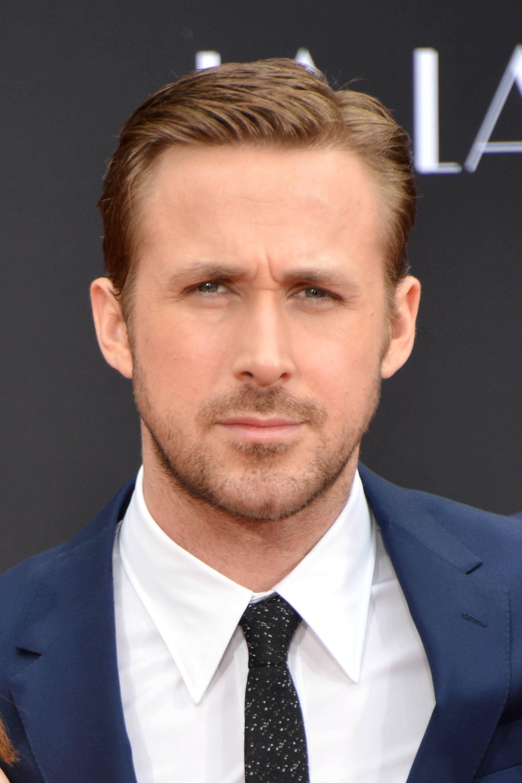 Coupe de cheveux Ivy League: Ryan Gosling aux cheveux châtain clair porté dans une coupe de cheveux Ivy League, vêtu d'un blazer bleu, d'une chemise blanche et d'une cravate