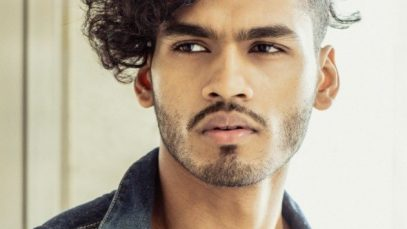 Man with dark brown medium-length curly hair with an undercut