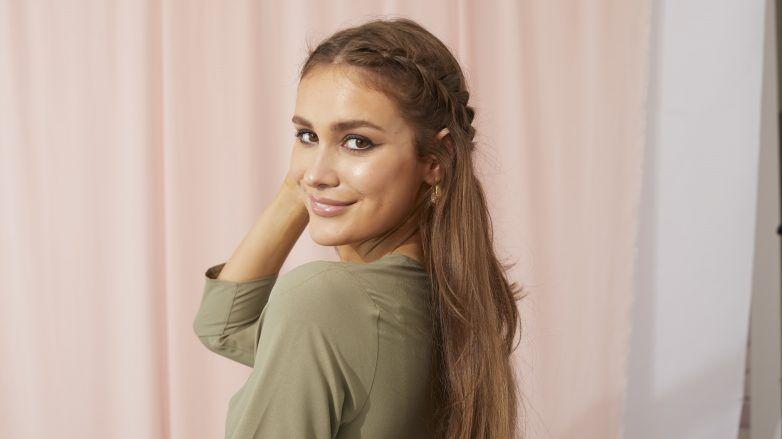 Femme touchant ses longs cheveux bruns en bonne santé