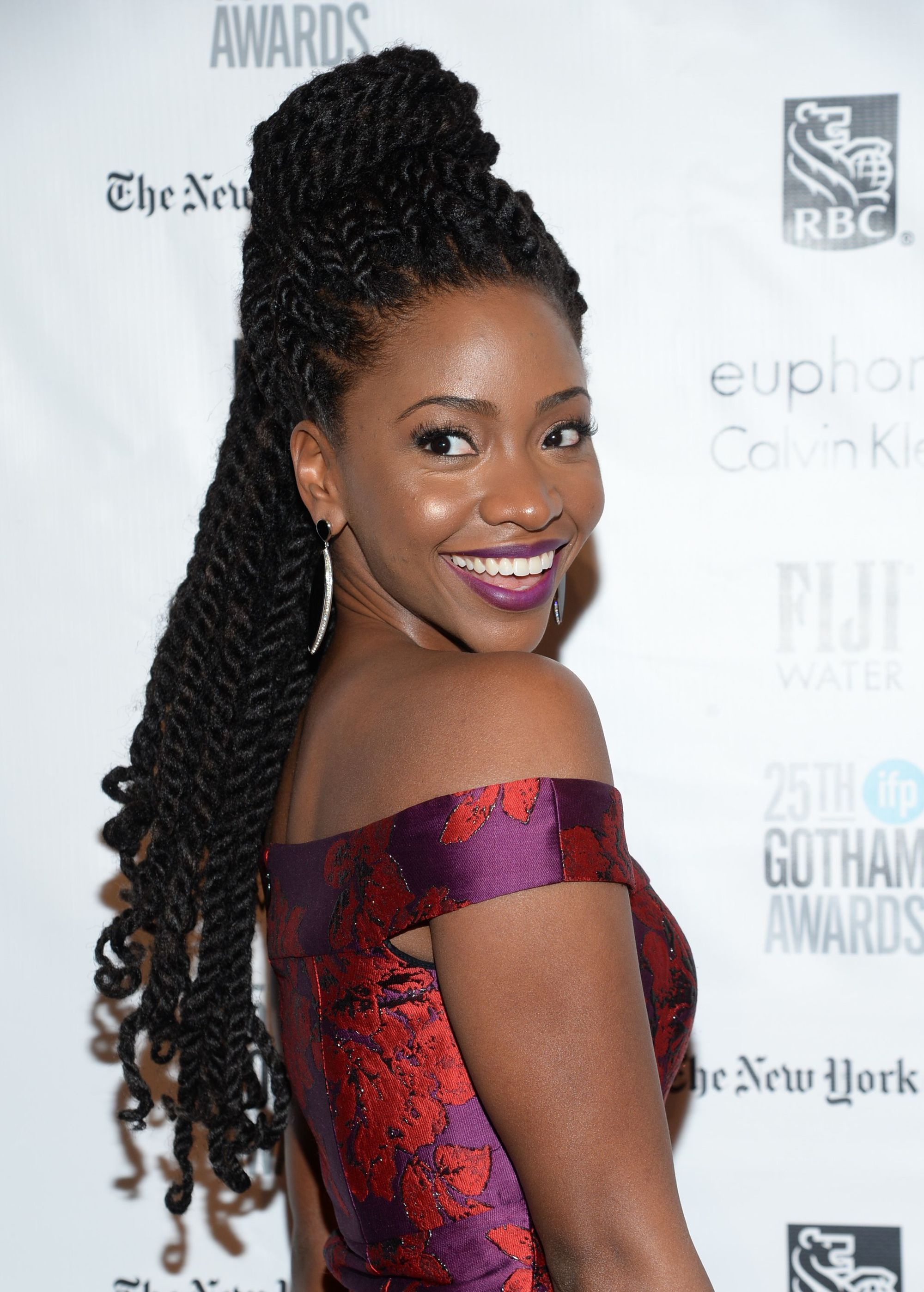 Shot of Teyonah Paris with half-up marley twists styled with curly ends, wearing a purple dress
