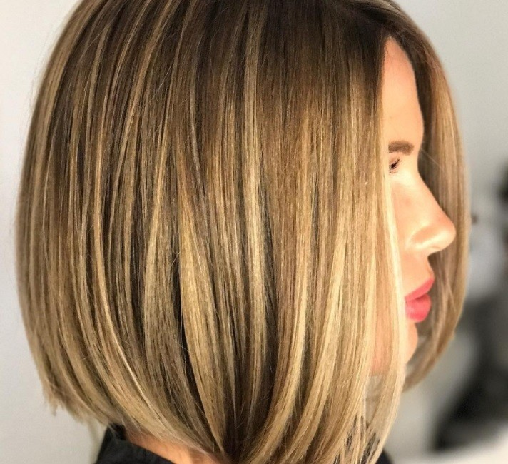 Layered bob: Side profile of a woman with a bronde highlighted sleek bob with layers