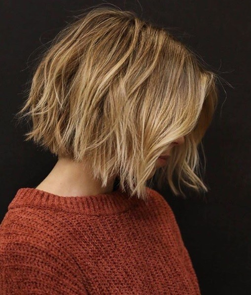 Layered bob: Side view of a woman with a blonde/light brown messy layered bob, wearing a rust orange jumper