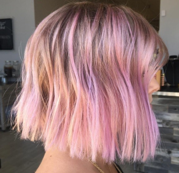 Layered bob: Side profile of a woman with a pink highlighted bob