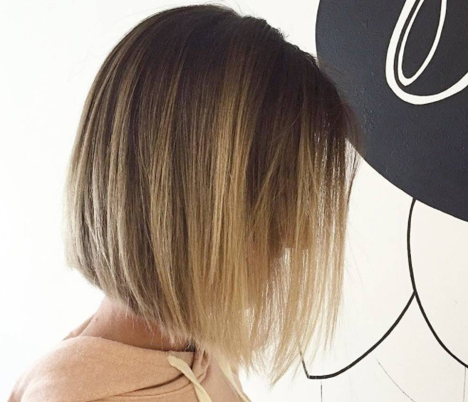 Layered bob: Side profile of a woman with a blonde bob hairstyle with layers