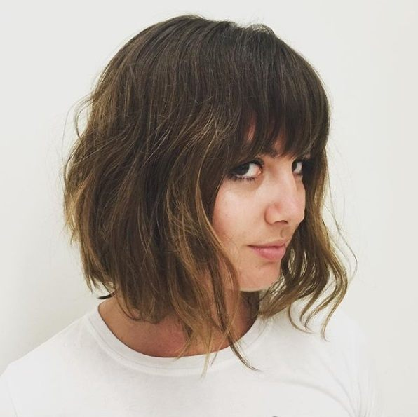 Layered bob: Woman with a brunette shaggy bob with a fringe, wearing a white t-shirt