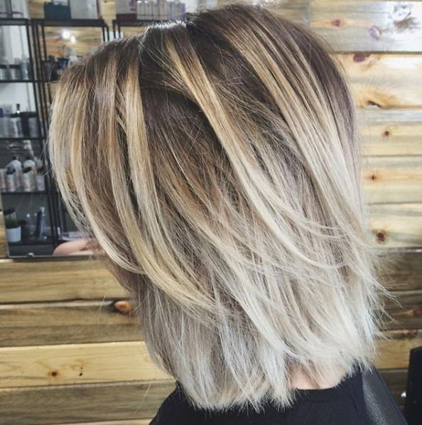 Layered bob: Side view of a woman with an ash blonde bob with long layers