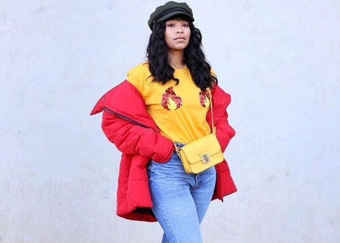 Coiffures protectrices pour cheveux naturels: gros plan d'une femme avec une veste rouge, haut jaune, portant une perruque et un chapeau de boulanger