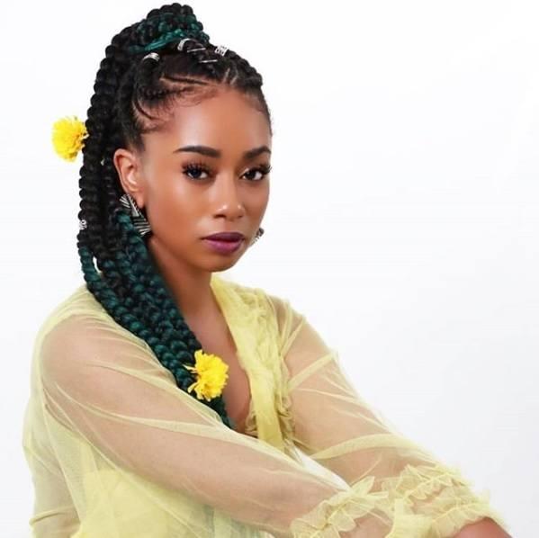 Coiffures protectrices: Femme avec ses cheveux naturels dans une queue de cheval tresse Ghana avec des fleurs jaunes dedans