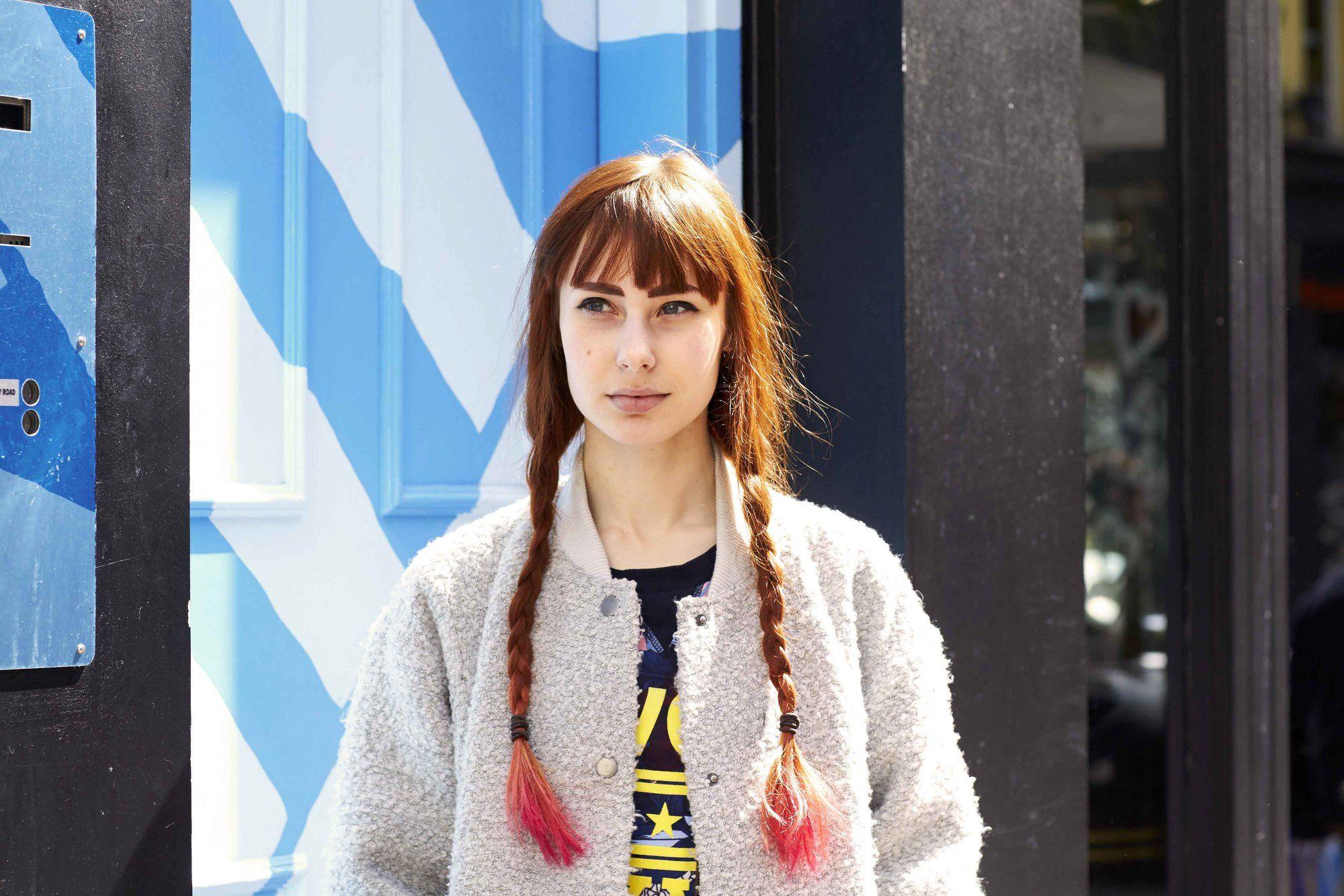Coiffures faciles pour cheveux longs: Femme aux longs cheveux bruns auburn coiffés de nattes tressées avec des pointes rose fluo.