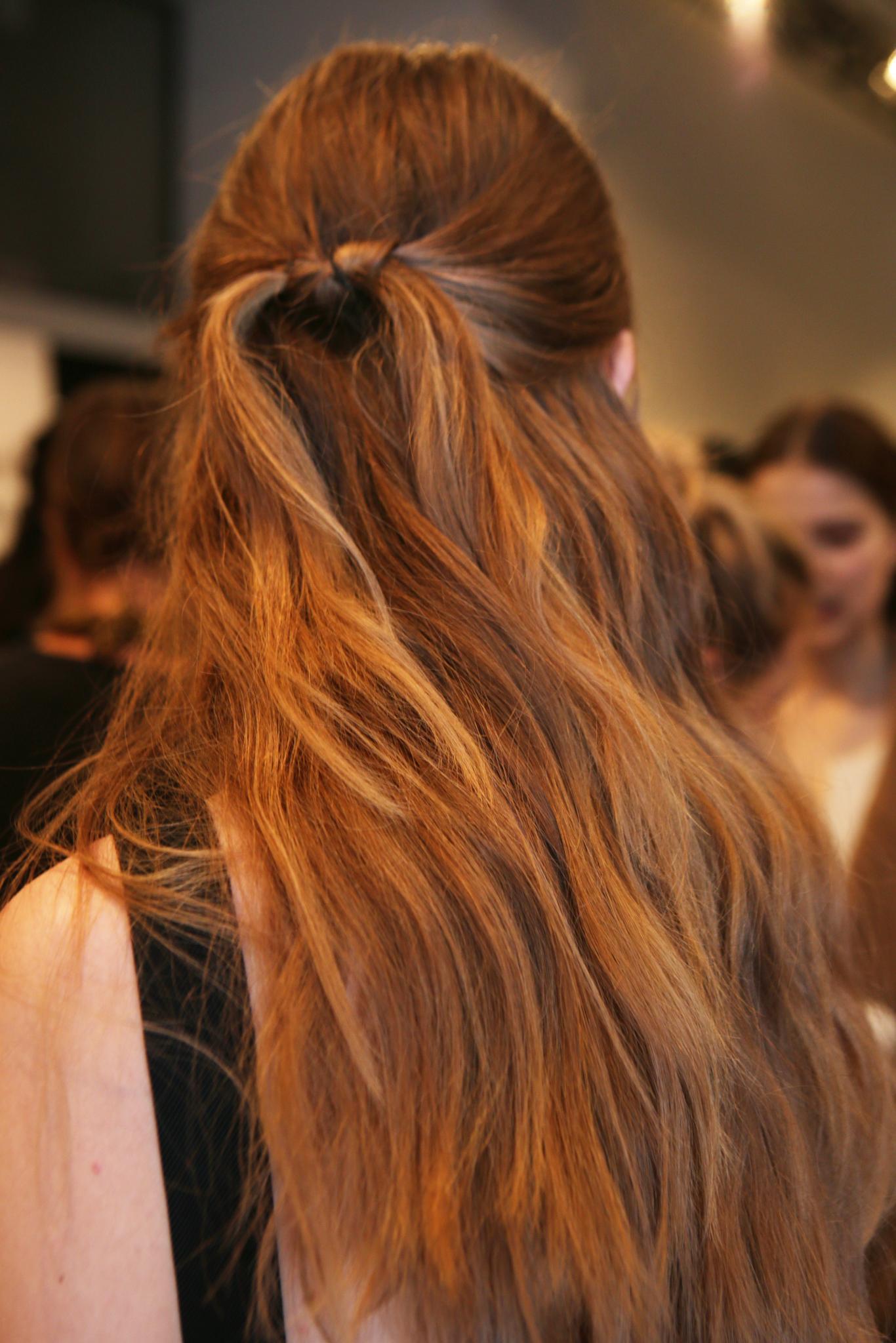 Coiffures faciles pour cheveux longs: modèle Backstage avec des cheveux longs dans une coiffure nouée mi-haut et mi-bas.