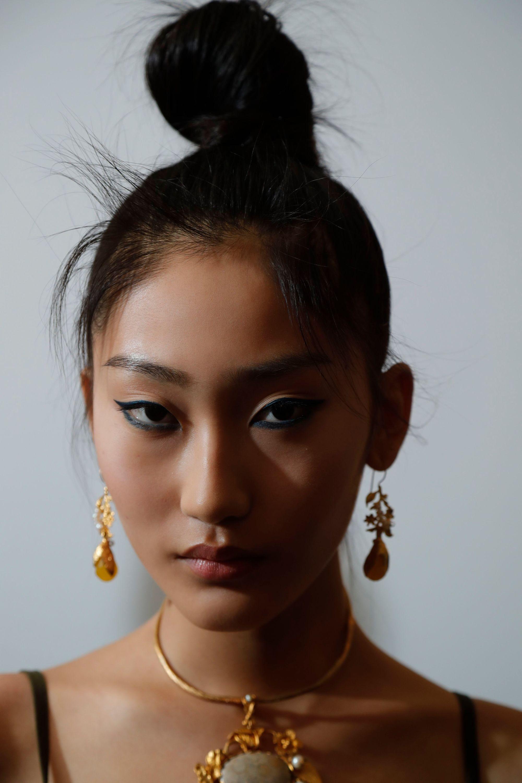 Coiffures faciles pour les cheveux longs: Femme aux cheveux raides brun foncé dans un chignon haut avec des boucles d'oreilles pendantes.