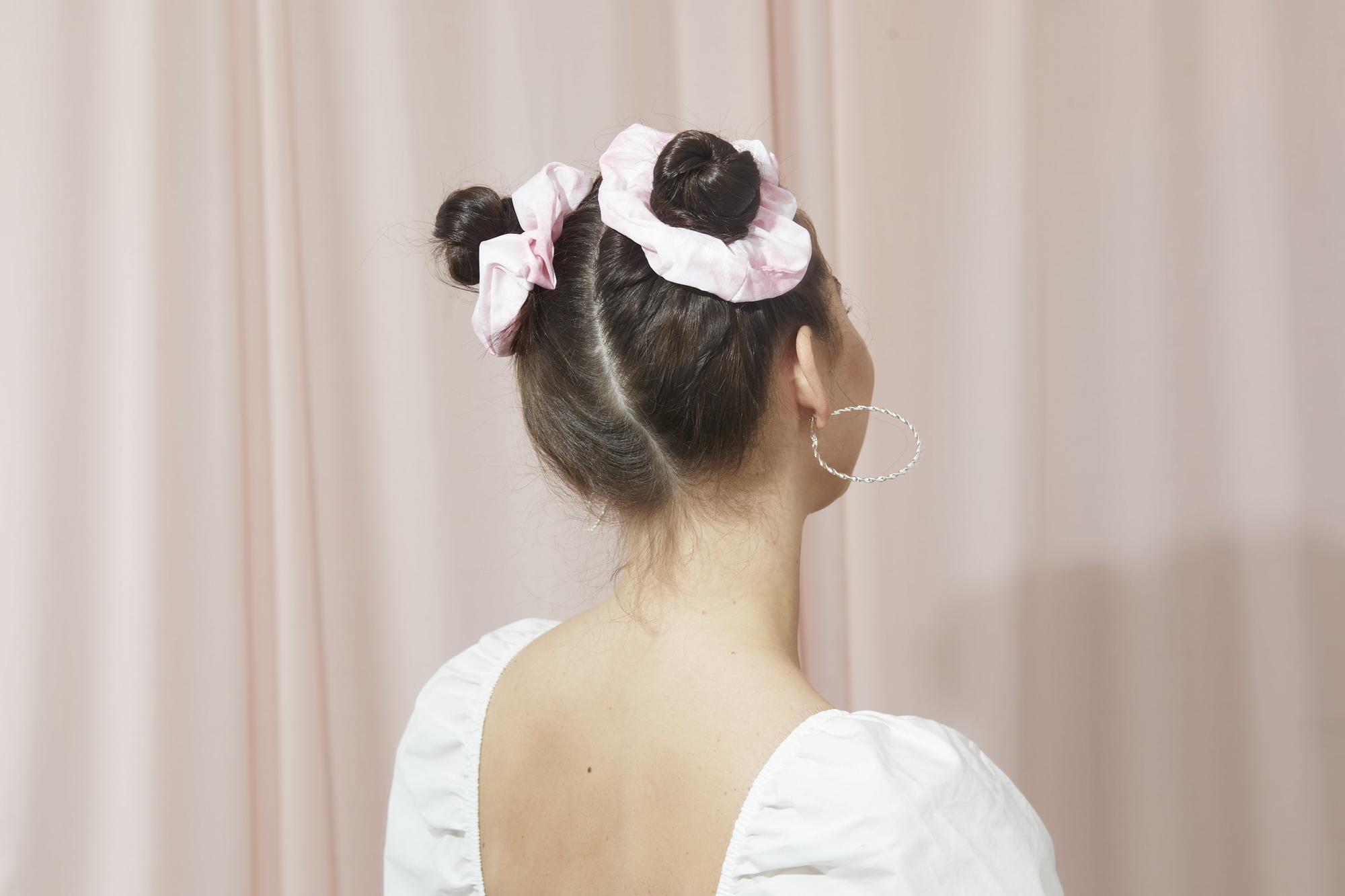 Femme aux cheveux bruns foncés en petits pains de l'espace avec des chouchous