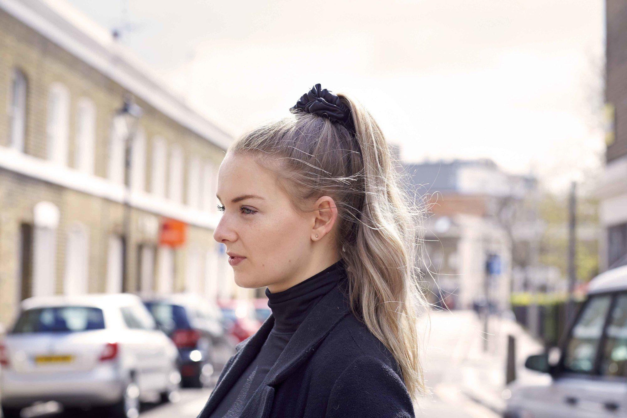 Coiffures faciles pour les cheveux longs: Femme aux cheveux ondulés surlignés blonds en queue de cheval haute avec un chouchou noir portant un haut à col roulé noir et un blazer.