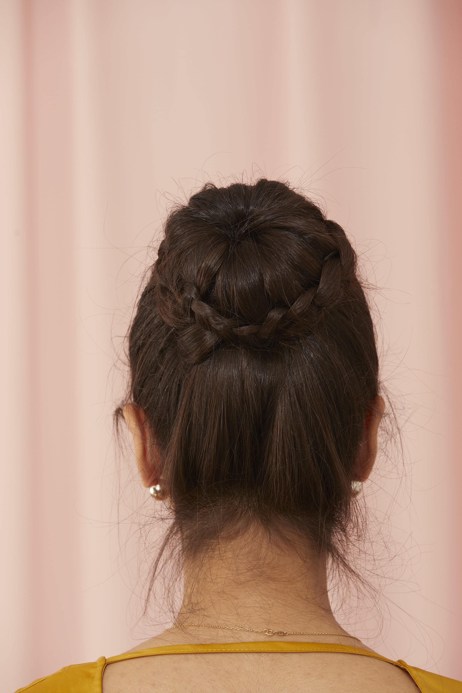 Femme aux cheveux longs en chignon tressé