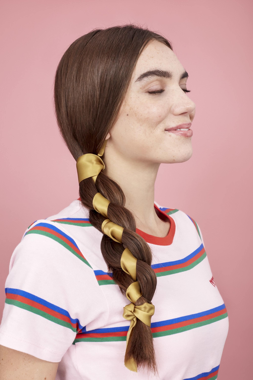 Coiffures faciles pour cheveux longs: Femme aux cheveux bruns raides en tresse d'écharpe latérale portant un t-shirt à rayures.
