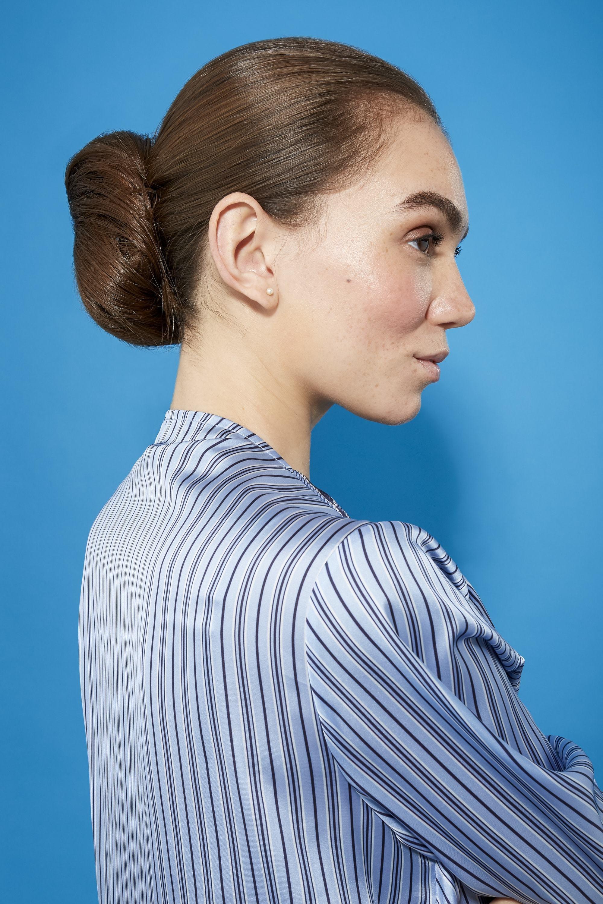 Coiffures faciles pour cheveux longs: Femme aux longs cheveux bruns droits dans un chignon bas en forme de beignet vêtue d'une chemise bleue à rayures.