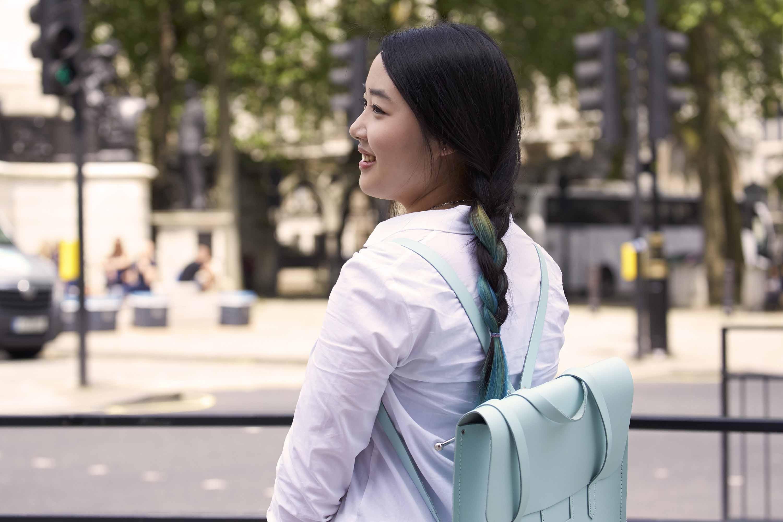 Coiffures faciles pour cheveux longs: femme aux longs cheveux bruns foncés avec des reflets bleus coiffés d'une tresse portant un sac à dos bleu clair.