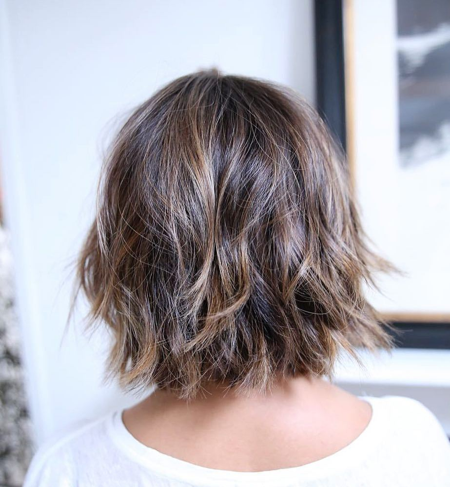 Woman with chestnut brown choppy bob with caramel highlights