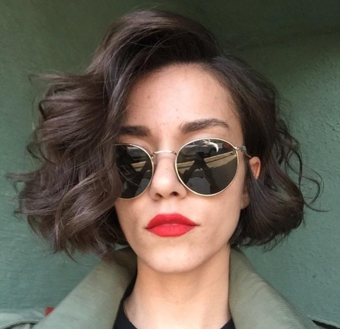 women with curly short choppy bob wearing sunglasses and red lipstick