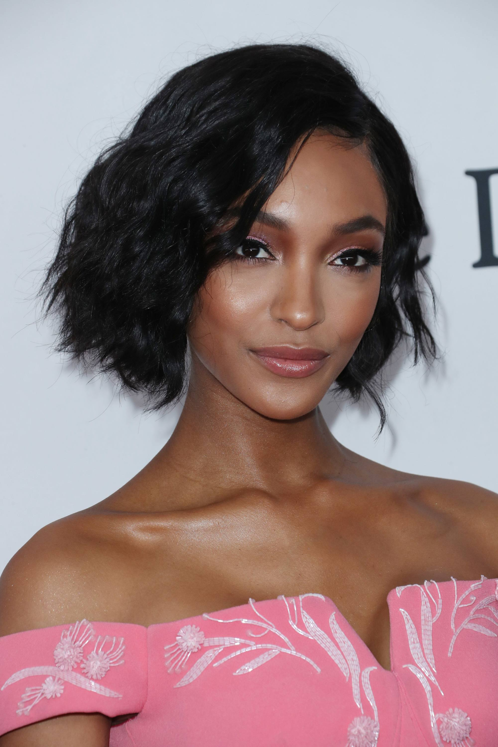 jourdan dunn textured dark brown choppy bob wearing pink strapless bardot dress