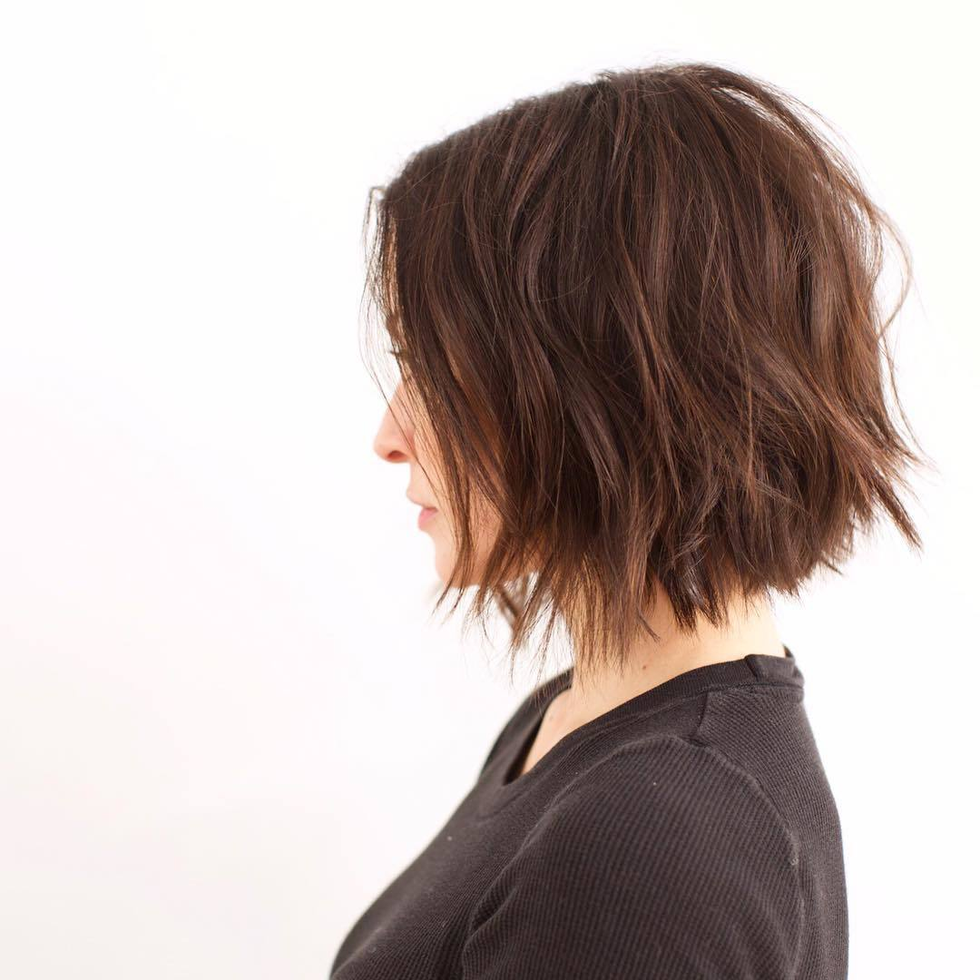 Woman with angled dark brown choppy short haircut
