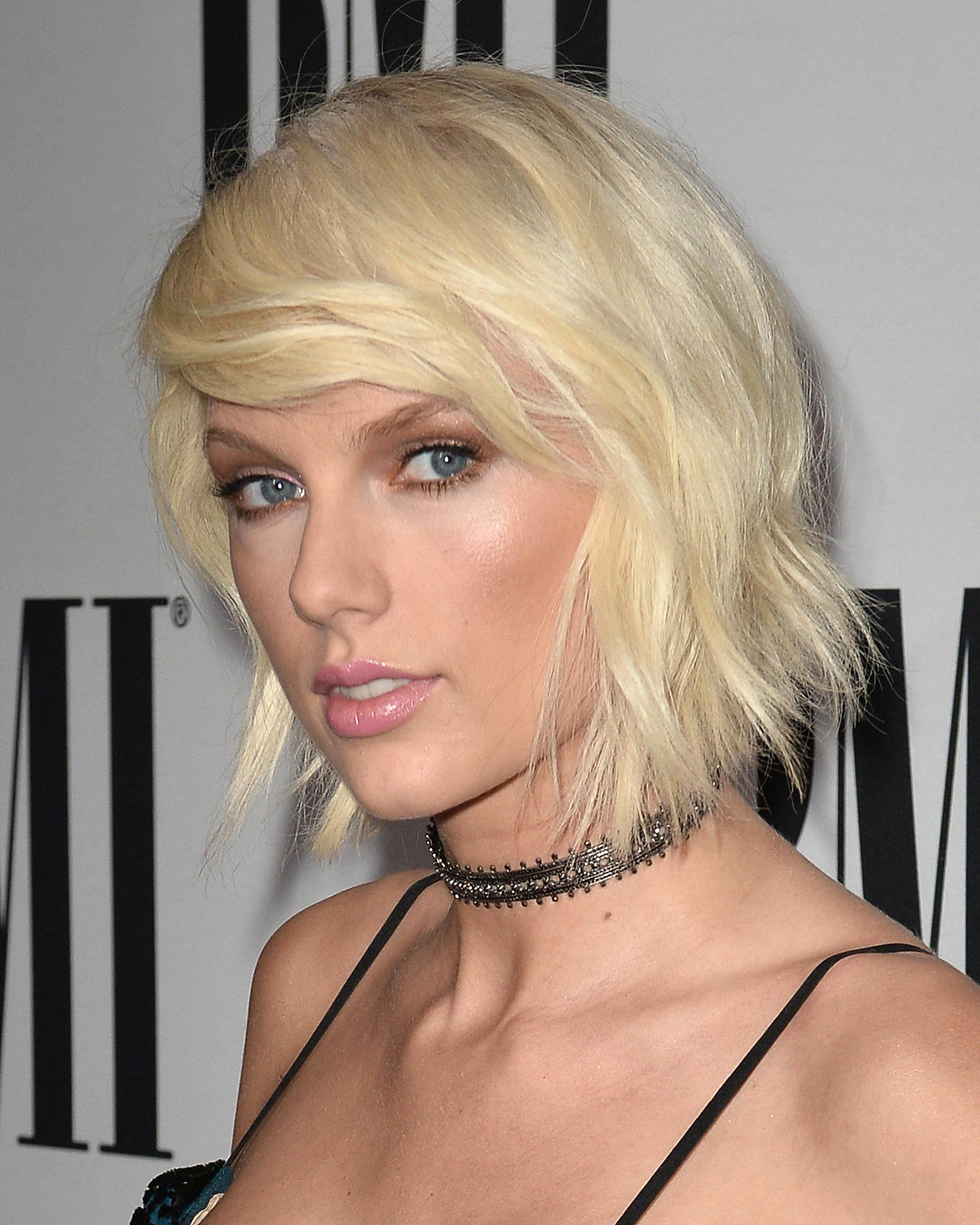 taylor swift with platinum blonde hair styled in a choppy bob with side bangs