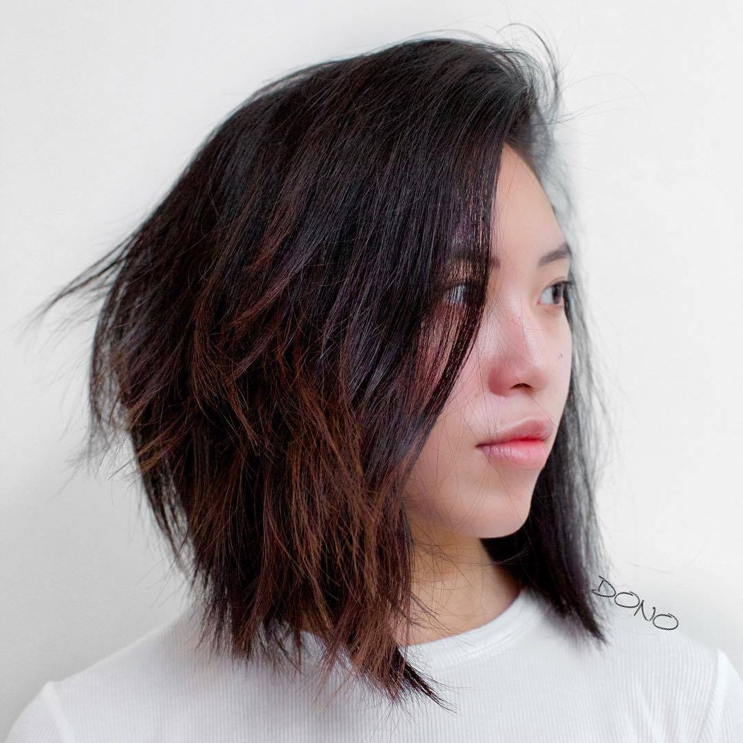 Woman with dark long choppy bob with highlights