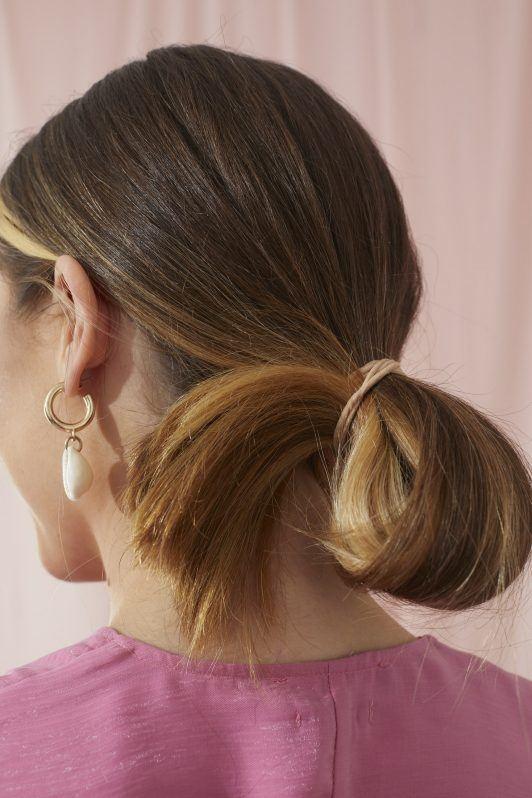 Femme aux cheveux longs en une queue de cheval en boucle