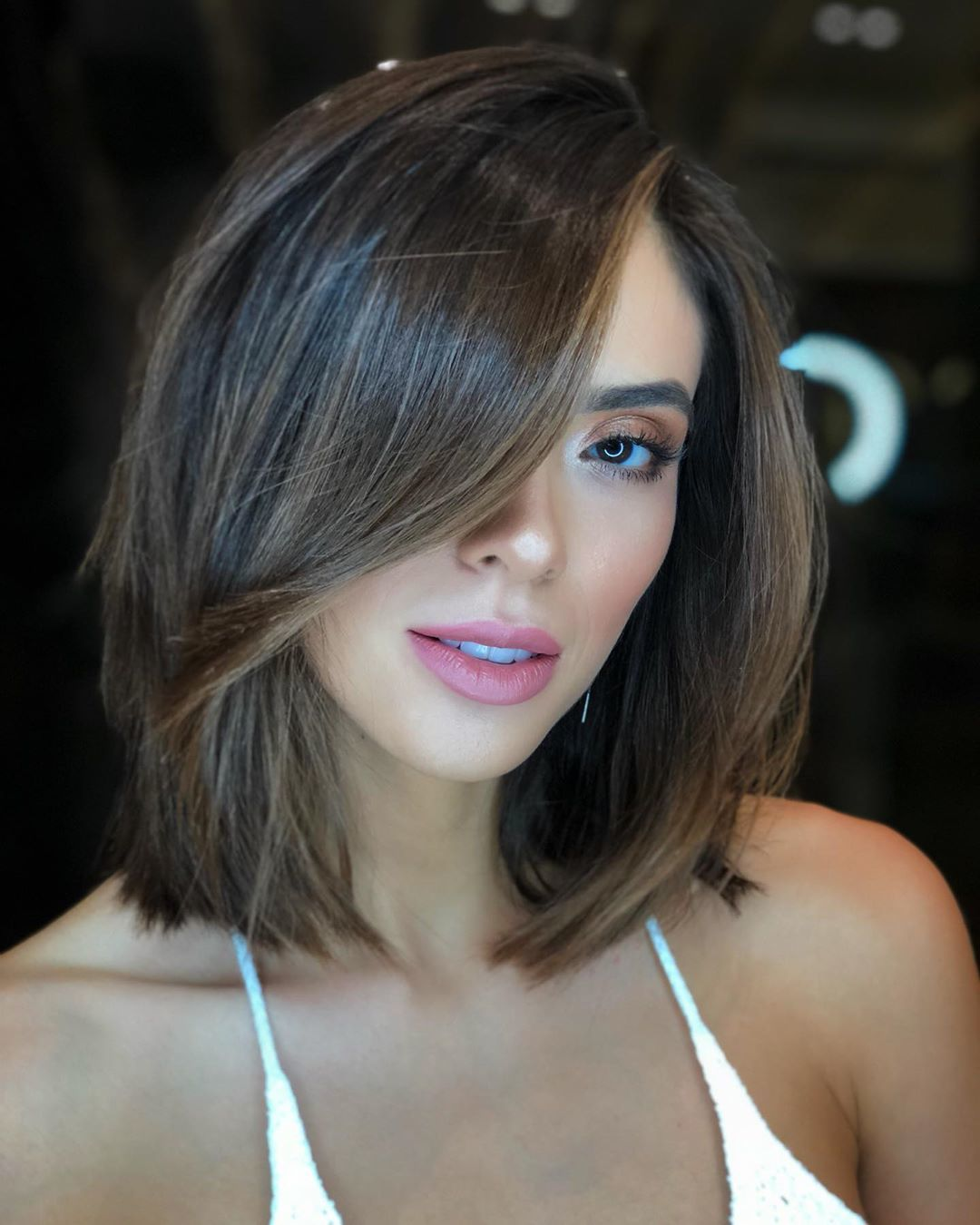 Woman with short bob dark brown hair with caramel highlights and long layers