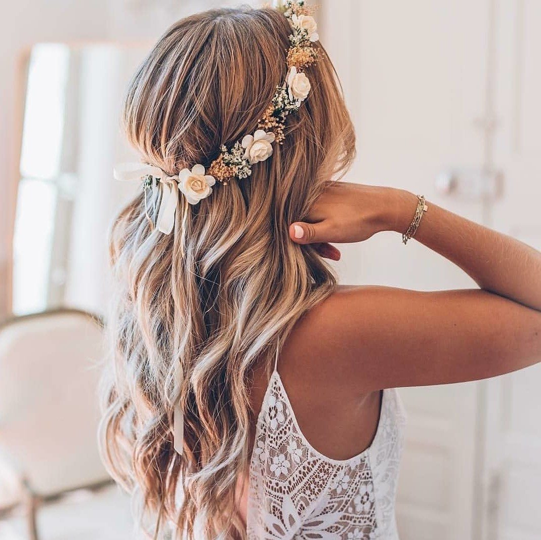 Wedding hairstyles: Woman with long bronde beachy waves with flower crown, wearing wedding dress and posing in a bedroom setting