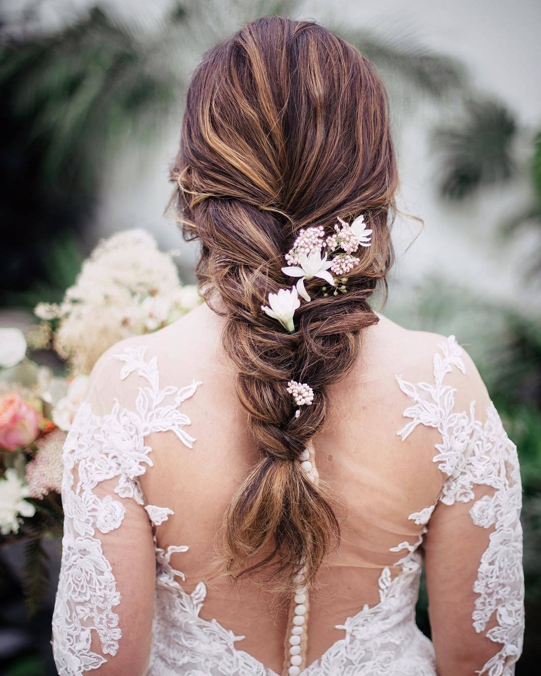 Wedding hairstyles: Woman with long chestnut hair styled into a loose braid with flowers in it, wearing wedding dress and posing outside