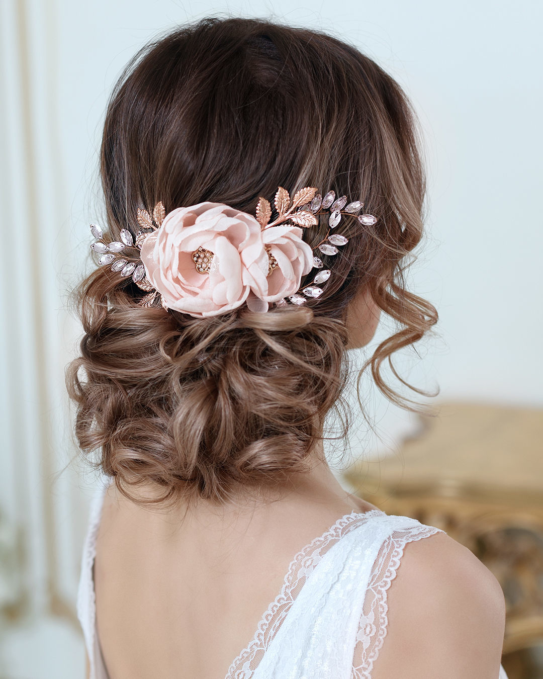 Wedding hairstyles: Woman with dark brown hair with highlights with her hair styled into a messy updo, with flowers in it, wearing a wedding dress