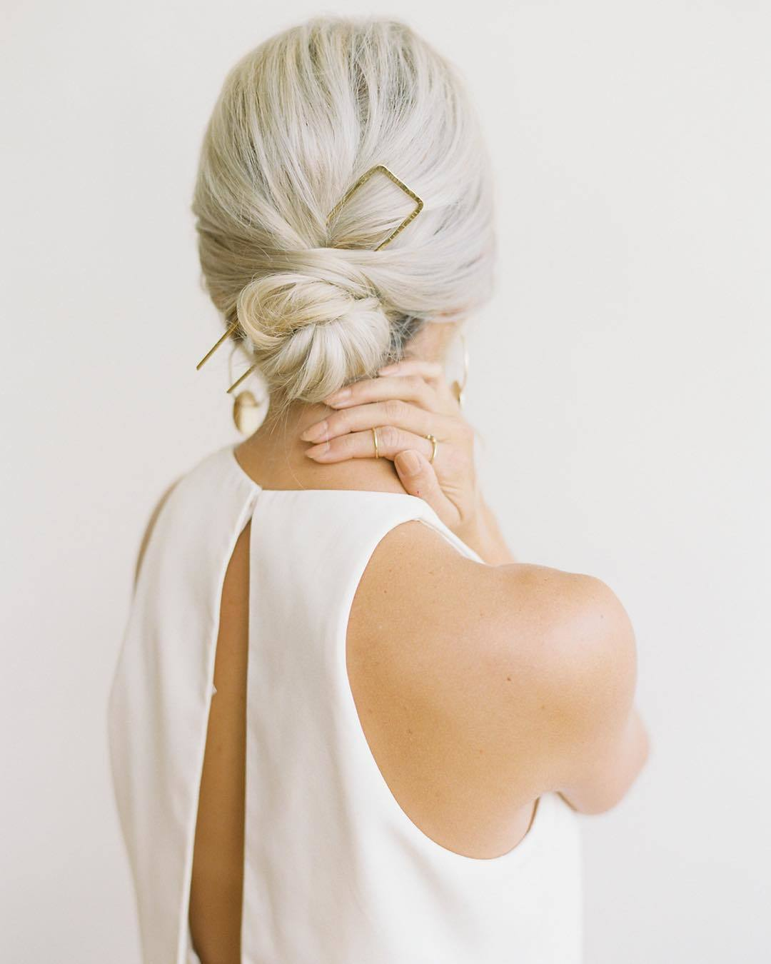 Wedding hairstyles: Woman with platinum hair styled into a sleek low bun, wearing a clip