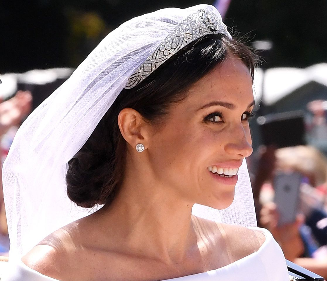 Meghan Markle Duchess of Sussex on her wedding day with her dark hair in a low messy bun with a veil and tiara