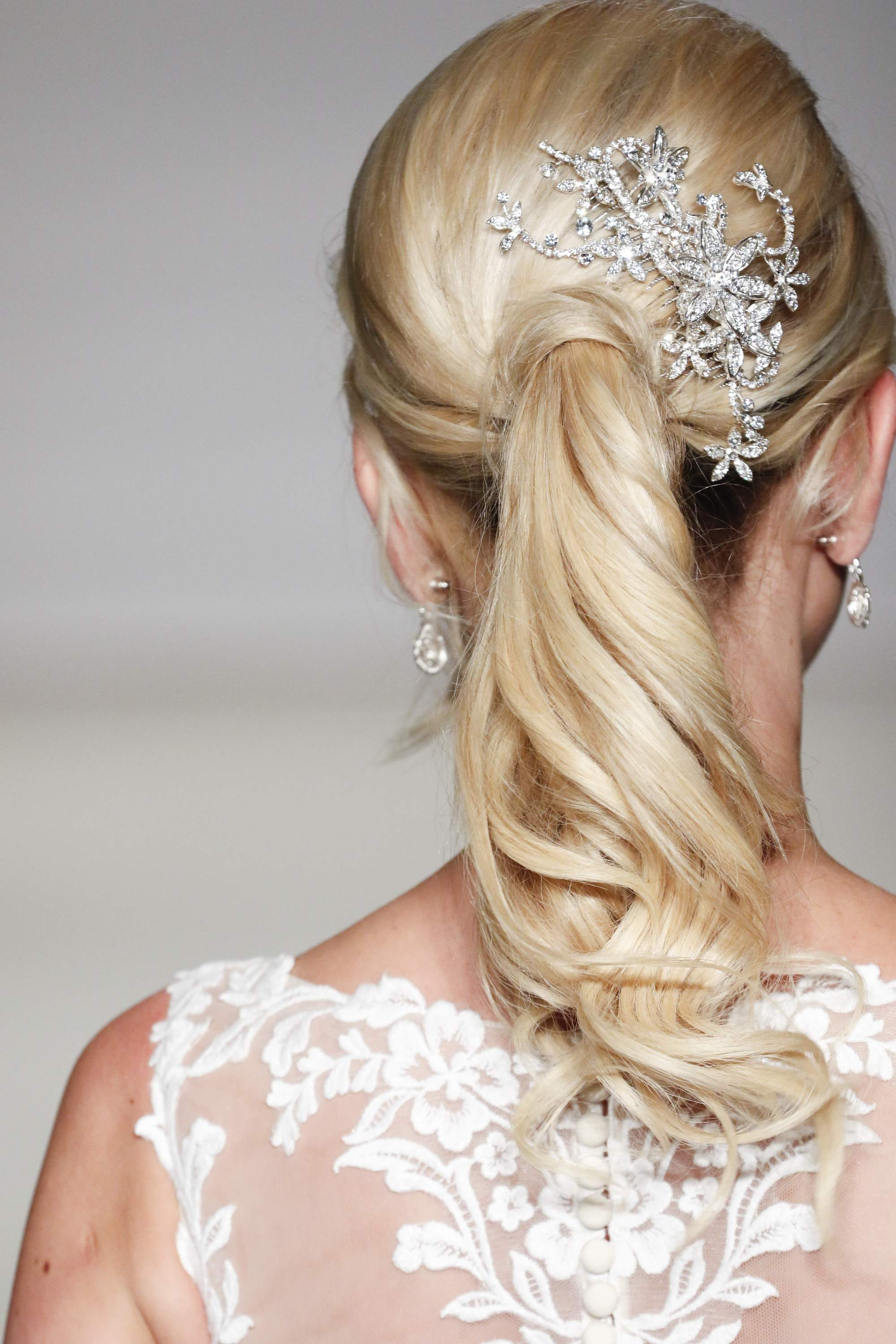 blonde bridal model with her hair in a curly ponytail with a hair accessory