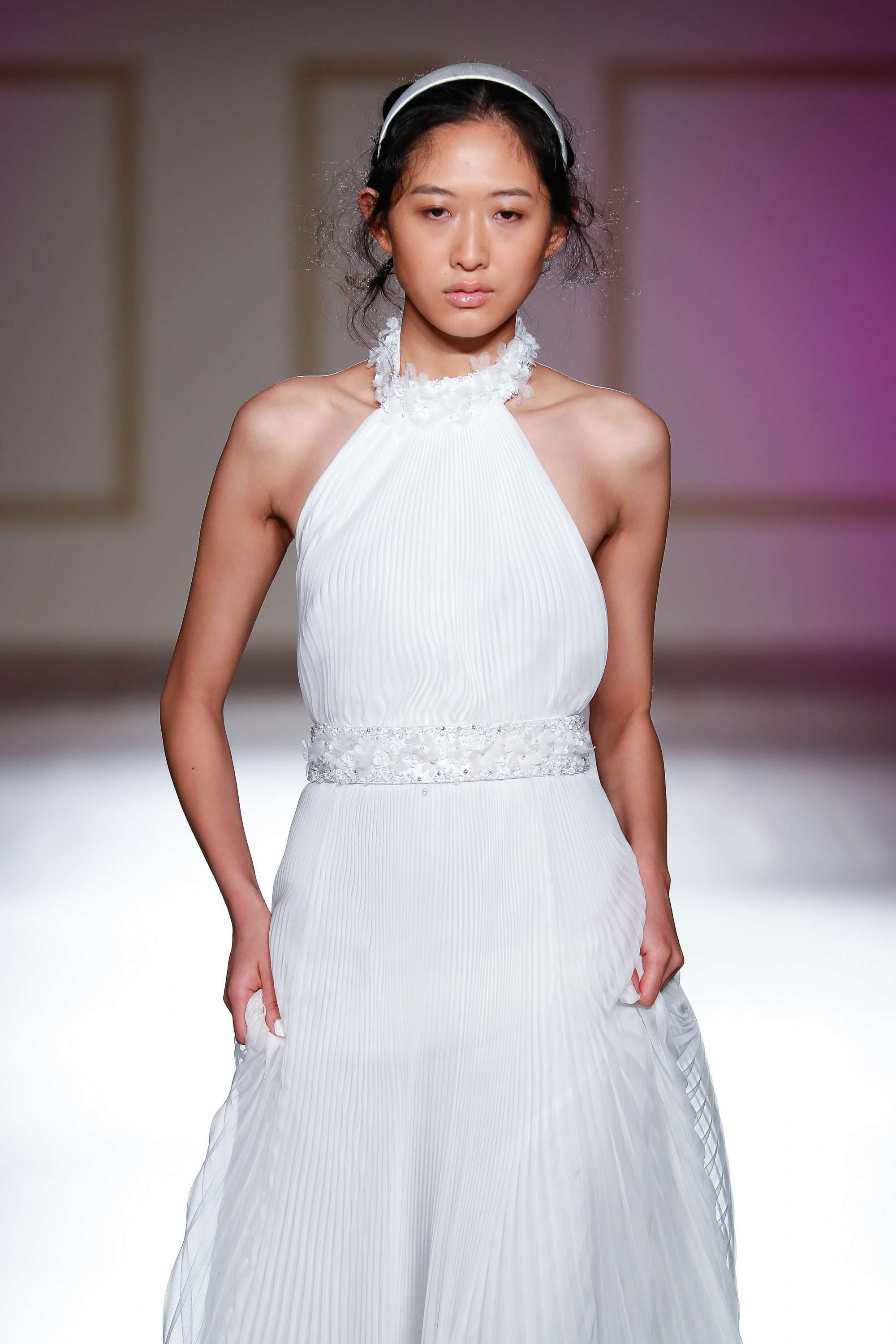 brunette bridal model on the runway with a white headband in her hair