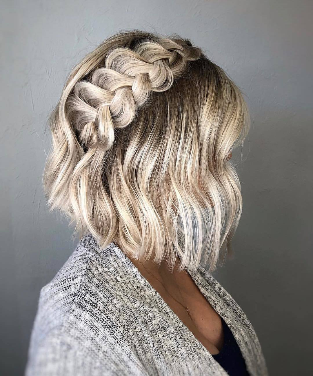 Short wedding hair ideas: Woman with short wavy bronde bob styled into a pinned Dutch braid, posing in a studio