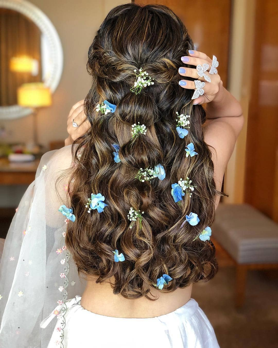 Indian wedding hairstyles: Woman with long flowing dark brown and highlighted hair styled into a half-up bubble with flowers in it