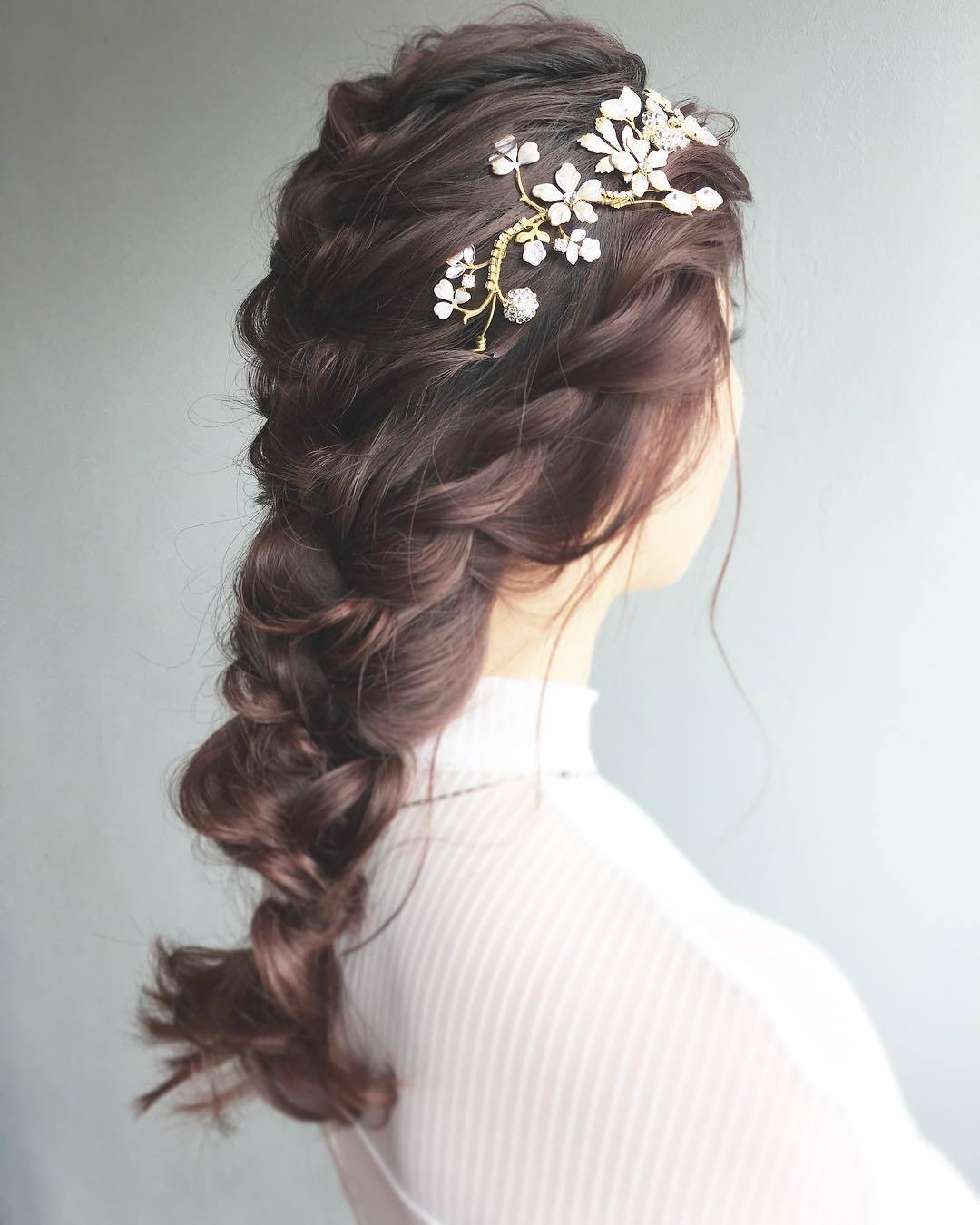 Bridal hairstyles: Woman with long mahogany coloured loose French braid with side flowers in it posing in a studio