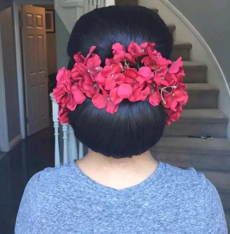 Bridal hairstyles:Woman with dark brown hair styled into floral chignon surrounded by red floral accessories