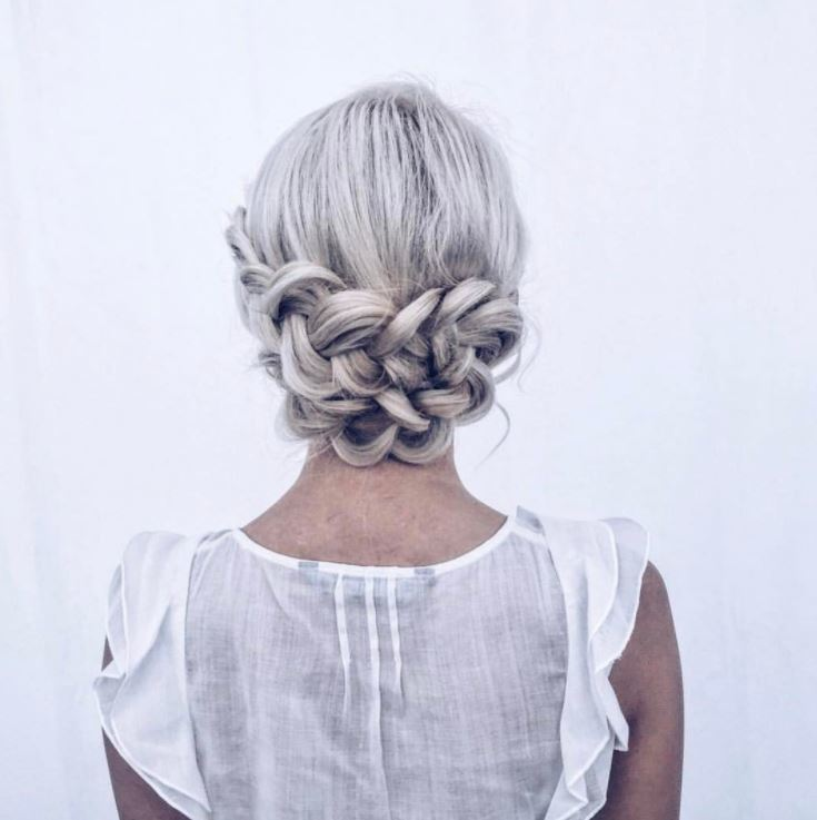 Bridal hairstyles: Woman with silver blonde hair styled into a low braid wrap