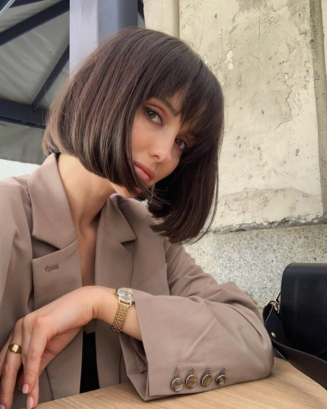 Woman with dark brown short French bob hair with wispy bangs