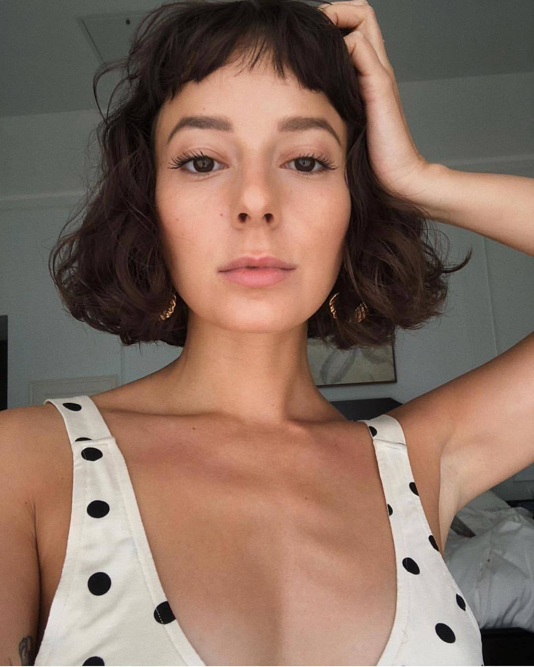 Woman with curly short bob with choppy micro fringe