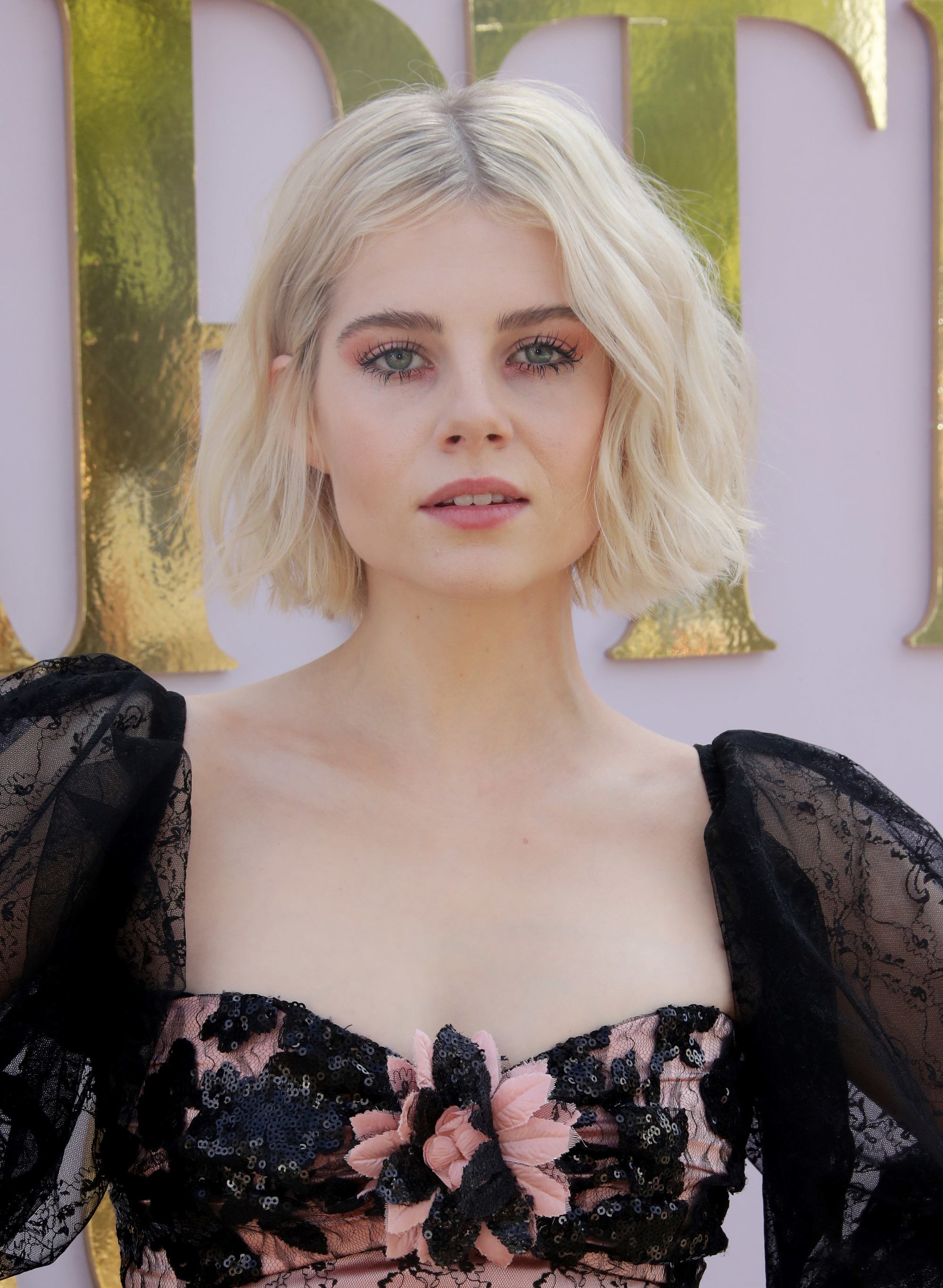 Lucy Boynton with platinum blonde wavy bob haircut