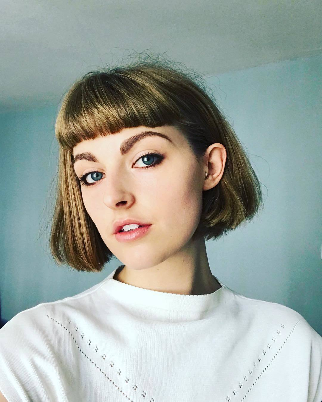 Woman with bronde short sleek bob haircut with micro bangs