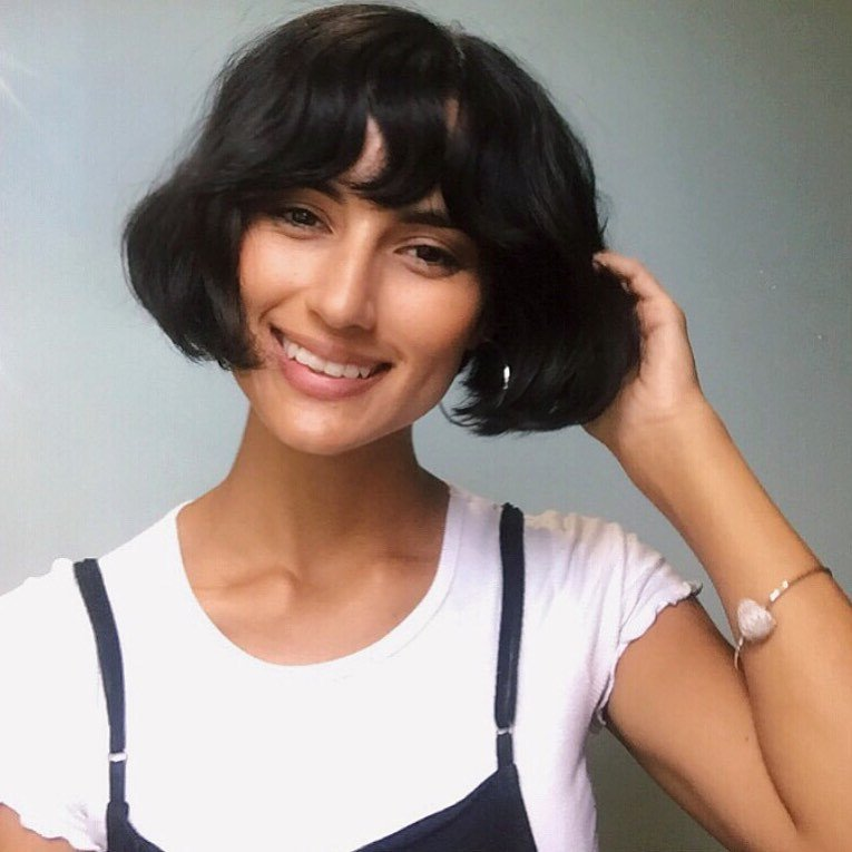 Woman with thick hair cut into a short curled bob style with bangs