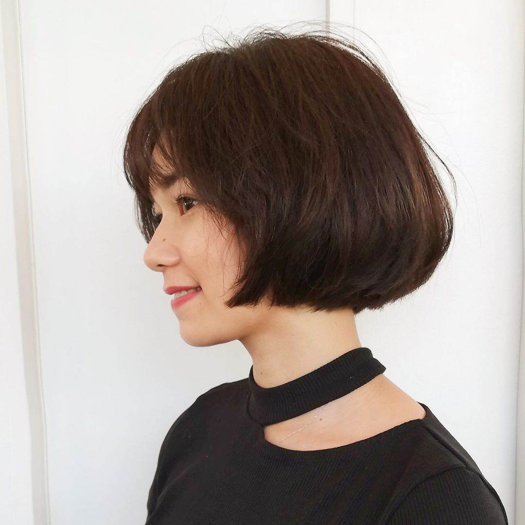 Woman with thick messy dark brown bob with wispy fringe