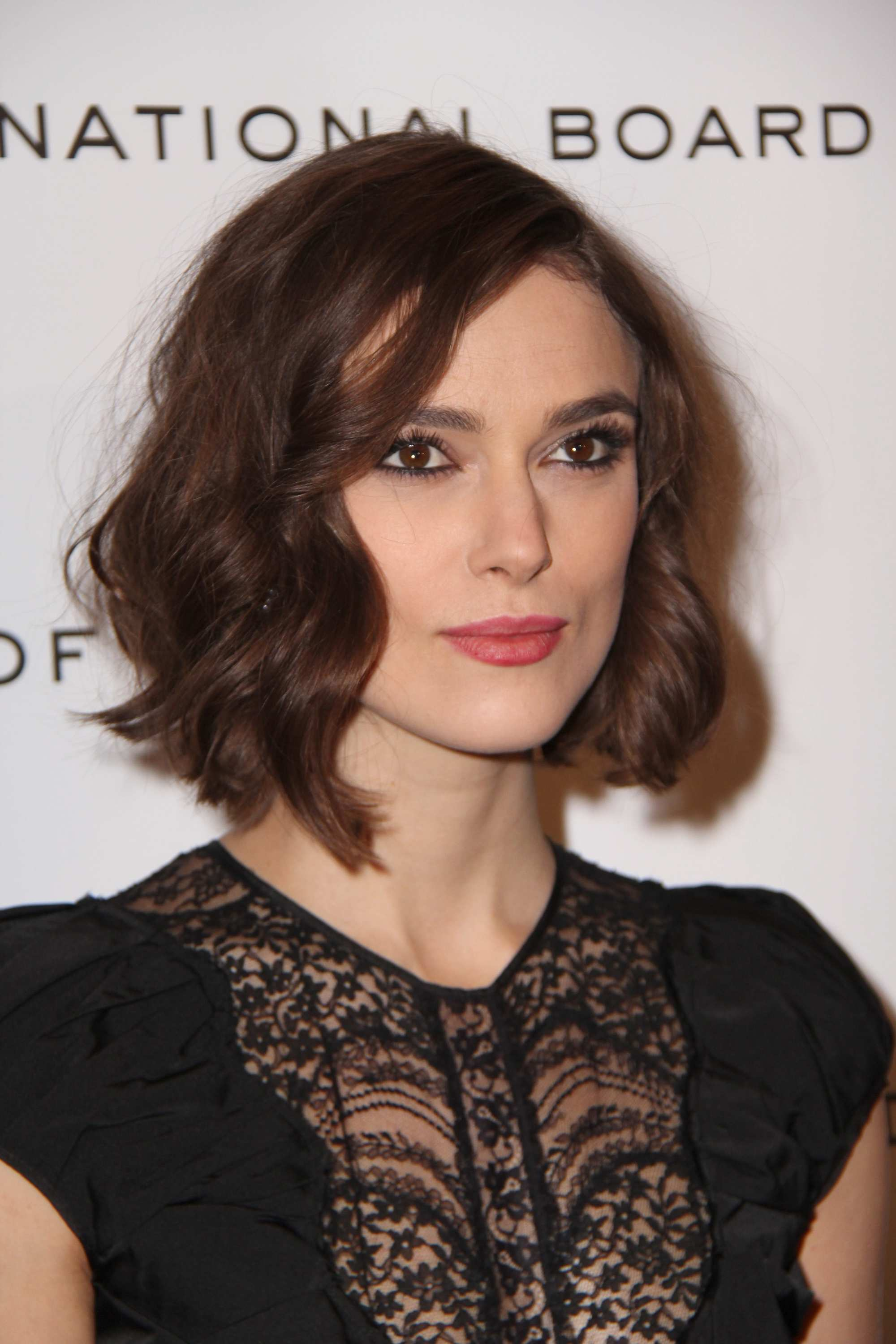 Keira Knightley with a brunette wavy bob with side-swept curled bangs