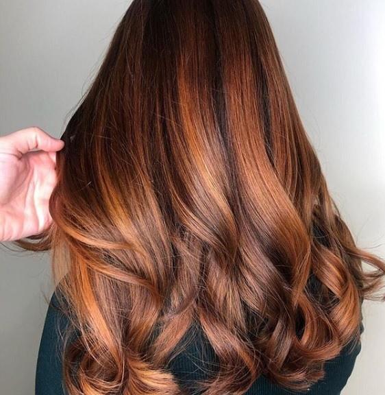Faits saillants en cuivre: vue arrière d'une femme avec de longs cheveux de balayage en cuivre, coiffés de boucles douces